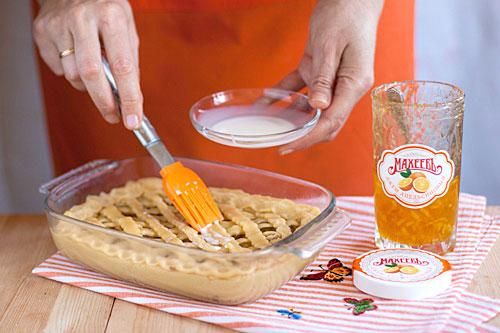 """Переносим """"решётку"""" с помощью скалки на пирог, защипываем по кругу края. Берём яичный желток, молоко и соль на кончике чайной ложки, перемешиваем. Такая намазка делает вкусную хрустящую корочку на пироге. С помощью кисточки наносим смесь на пирог, равномерно на всё тесто сверху. Ставим пирог в нагретую до 180 градусов духовку и выпекаем до румяности около 30-40 минут."""