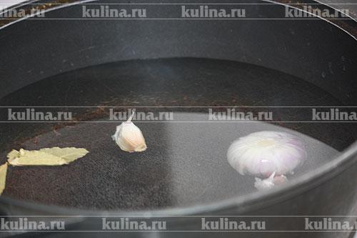 В кастрюлю налить воду, добавить соль, положить лук, лавровый лист и чеснок, довести до кипения. Влить коньяк.