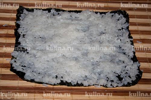 Заранее приготовить рис для суши. Отступить от края 1 см. и выложить рис.