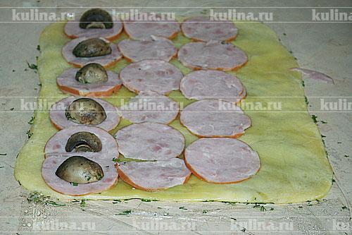 Ветчину нарезать тонкими ломтиками, грибы разрезать пополам или тоже тонкими ломтиками.На подготовленный пласт сыра выкладываем ветчину, грибы.