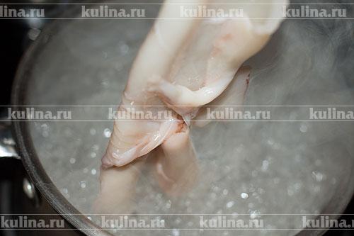 Кальмаров разморозить, снять тонкую кожицу, удалить внутренности, промыть. Вскипятить подсоленную воду, опустить кальмаров, варить 1 минуту и вытащить, остудить.
