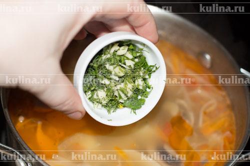 Приготовить заправку для щей. Для этого соедините в миске мелко нарезанную зелень, чеснок и оливковое масло, смесь хорошенько посолите. Выложить заправку в щи и снять их с плиты. Дать постоять минут 10.