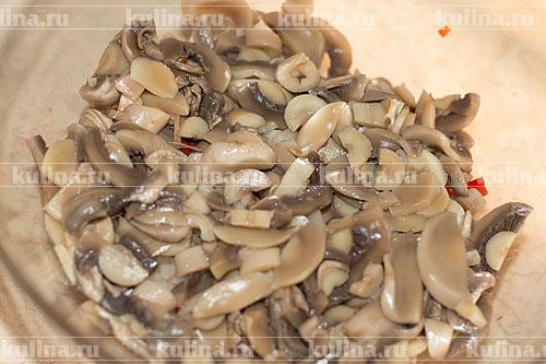 Шампиньоны нарезать ломтиками и положить к остальным ингредиентам.