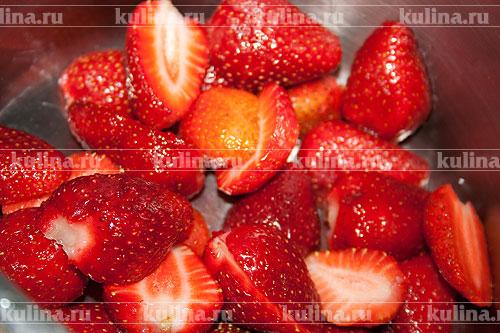 Клубнику очистить, удалить плодоножки и каждую ягоду разрезать пополам. Выложить ягоды в миску.