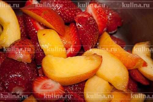Персики разделать на половинки, удалить косточки, разрезать на дольки, выложить к клубнике.