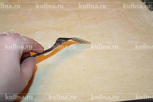 Переложить тесто на противень, смазанный водой. Сделать вилкой проколы в нескольких местах. Поставить в духовку, разогретую до 225-230 градусов.