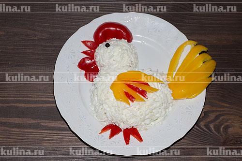 Из красного перца вырезаем клюв, гребень, сережки и ножки. В качестве глаза используем черный перец или ягоду можжевельника. Из желтого вырезаем хвост и крыло. Оформляем салат так, как показано на фото.