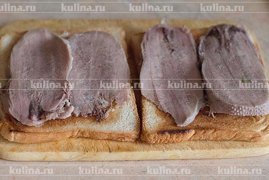 Выложить на хлеб ломтики языка.