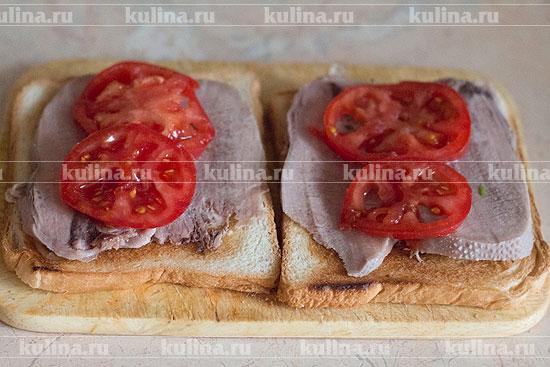 Томат разрезать на 4 ломтика и выложить по 2 на каждый бутерброд.
