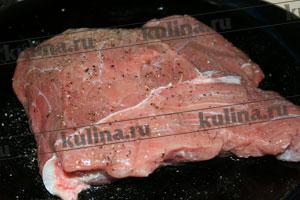 Мясо натереть молотым черным перцем и